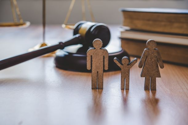 wooden figurines of a family on a desk in front of a gavel